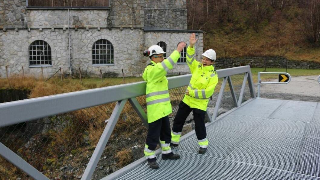 HIGH-FIVE: Per Magne Gullaksen har vore prosjektleiar for å få på plass brua over Tya, Anneli Nesteng er kraftverksjef i Hydro Energi. Måndag opna dei den nye brua over Tya på Moa med ein high-five. Foto: Ole Ramshus Sælthun