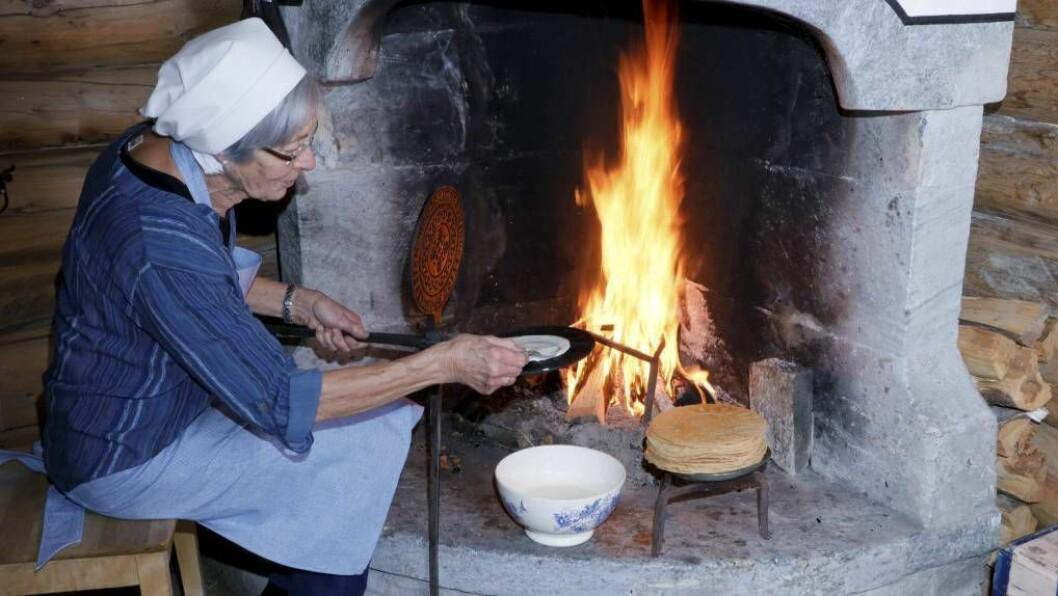 Forfattar Bjørg Nordset steikjer kaker på gamlemåten over open eld. Foto frå boka: Bjarne Fossøy