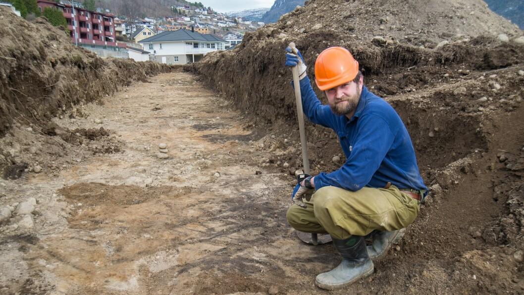 TYDELEGE SPOR: Arkeolog Glenn Heine Orkelbog sit på huk ved nokre mørke riss, spor etter den eldste forma for plog me kjenner til.