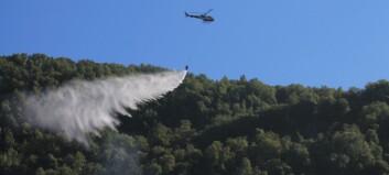 Helikopteret avsluttar dropp av vatn, brannmannskapet gjer søk i terrenget