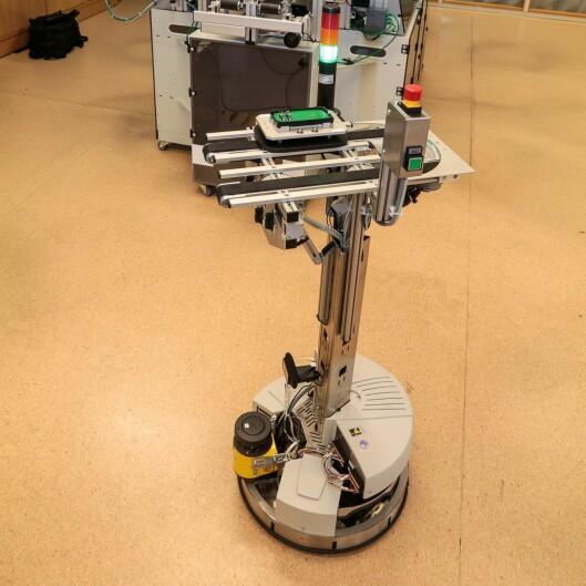 Ein «Robotino» eller AGV (Automated Guided Vehicle) transporterer produkta i øvingsfabrikken mellom dei ulike stasjonane. Å programmere denne, er ei oppgåve som elevane på VGS kan få jobbe med.