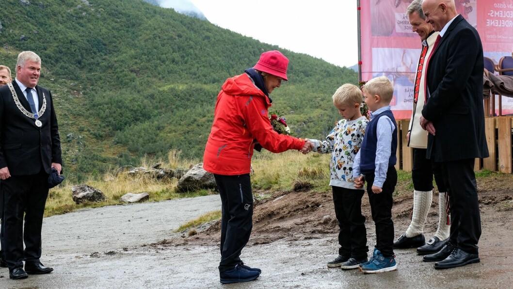 STORFINT BESØK: Ordførar Ivar Kvalen følgjer med når dronning Sonja takkar for blomane og velkomsten ho fekk av Tobias Fåberg og Kasper Nes, begge seks år gamle. Turlagsleiar Ole Schanke Eikum og bygdalagsleiar Asbjørn Nes til høgre.