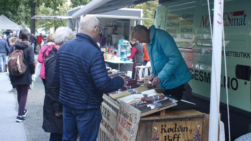 PENSJONERT PØLSEMAKAR: Kåre Haugland har selt pølser på Lærdalsmarknaden sidan 1994. Her serverer han ein smaksprøve til Rolf og Inger Solbakken.