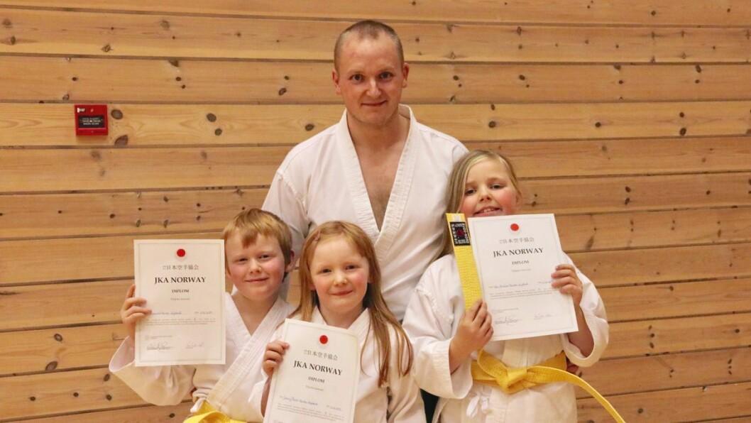 STOLTE: Andreas (8, t.v.), Jenny Marie (7, midten) og Ida Emilie (10, t.h.) Førde Systad var stolte over å ha sikra seg gult belte i karate måndag. Bak står far Jan André Førde Systad.