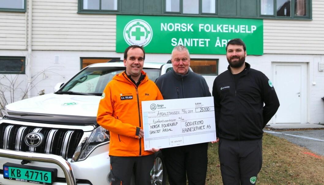 GÅVE: Glenn Morten Hestetun (midten) og Sognefjord Hamneservice AS tok på seg nisseoppdraget i år som i fjor, og gav ei gåve på 25.000 kroner til Norsk Folkehjelp Årdal.