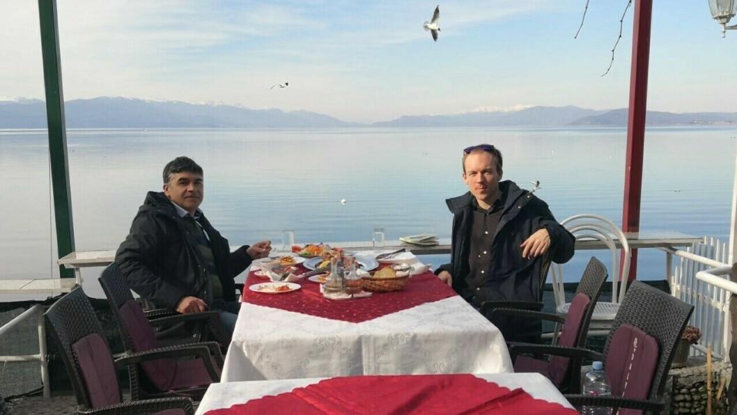 GOD UTSIKT: Den lokale guiden Aleksandar (t.v) og Snorre Sandemose (t.h) på lunsj ved Ohridsjøen i Nord-Makedonia.