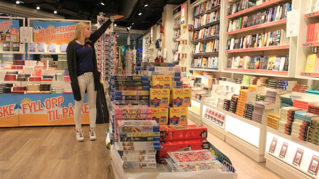 Butikksjef på Ark Linda Lund viser kor langt stabelen med puslespel gjekk for ikkje lenge sida. Sogningar har ekstra tid, og mange veljer å utfordra seg med puslespel.