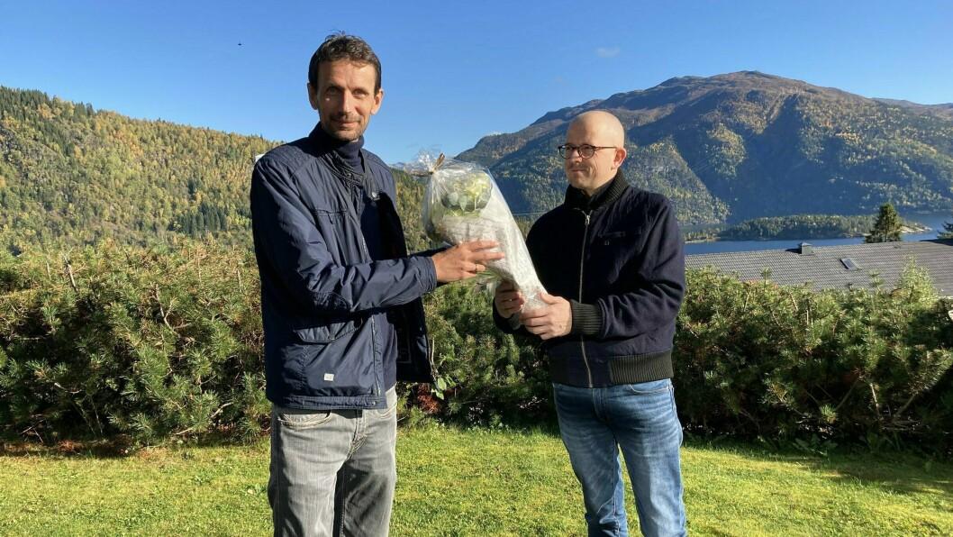 FAST TILSETT: Frode får blomster og gratulasjonar frå John Martin Høines, personalet sitt medlem i tilsetjingsutvalet.