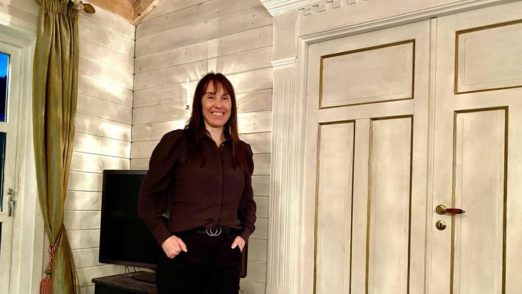 HEIME: Karine Kjørlaug i barndomsheimen på Lambhaug på Indre Hafslo. Huset er teikna av mora sjølv.