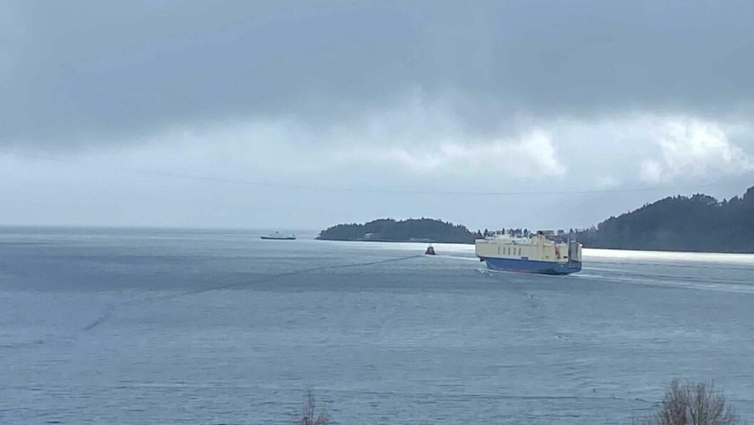 PÅ VEG: «Asian Emperor» har følgje av slepebåten «Stadt Kinn» på veg ut fjorden.